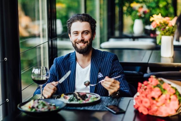 Homem bonito e sorridente comendo salade em restaurante e uma mulher esperando com um buquê de rosas