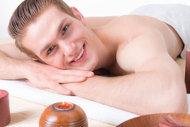 Homem bonito e sorridente deitado sobre as mesas de massagem no salão spa e relaxar. conceito de tratamento de beleza.