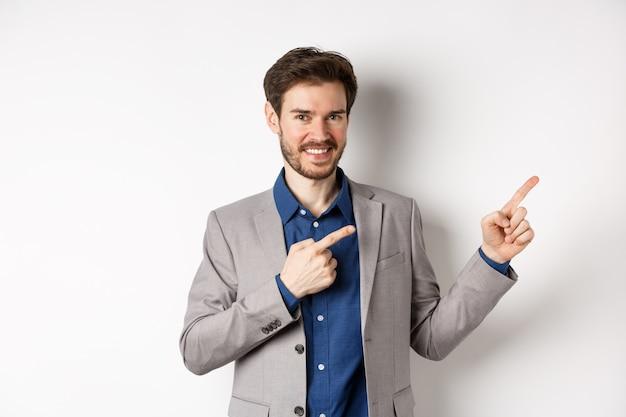 Homem bonito e sorridente em um terno de negócio, apontando os dedos no canto superior direito, mostrando o logotipo, a empresa de publicidade, de pé sobre um fundo branco.