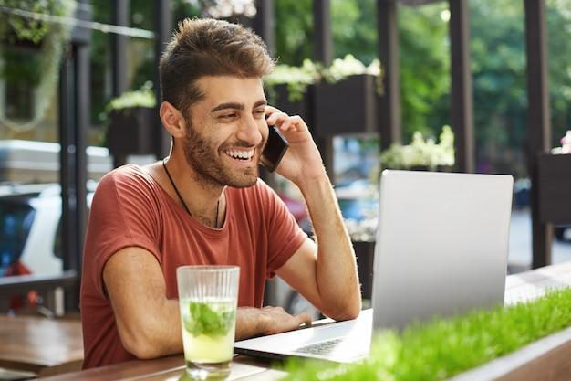 Homem bonito e sorridente falando no celular, ligando para um vendedor que encontrou online enquanto usava um laptop, fazia compras, pesquisava um apartamento na internet