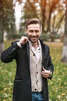 Homem bonito e sorridente feliz endireita as laterais de seu casaco azul escuro. jovem freelancer em pé