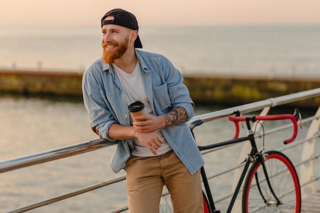 Homem bonito e sorridente hipster barbudo ruivo vestindo camisa jeans e boné com bicicleta no nascer do sol da manhã à beira-mar bebendo café, viajante saudável estilo de vida ativo