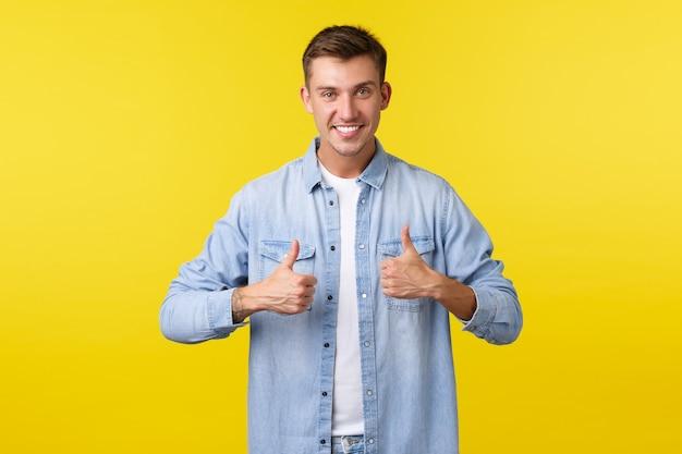 Homem bonito e sorridente loiro mostrando o polegar para cima, encorajar a pessoa, torcendo por você. prazer em recomendar produto, deixar feedback positivo, curtir e aprovar serviço, fundo amarelo.