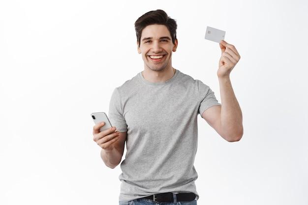 Homem bonito e sorridente mostrando um cartão de crédito de plástico e usando o smartphone para pagar online, fazendo compras no aplicativo, parado satisfeito contra uma parede branca
