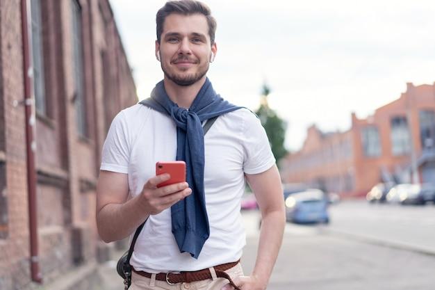 Homem bonito e sorridente ouvindo música enquanto caminha pela cidade