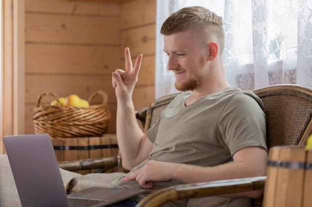 Homem bonito e sorridente se comunica com os pais na internet usando um laptop