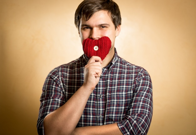Homem bonito e sorridente segurando um coração vermelho na boca