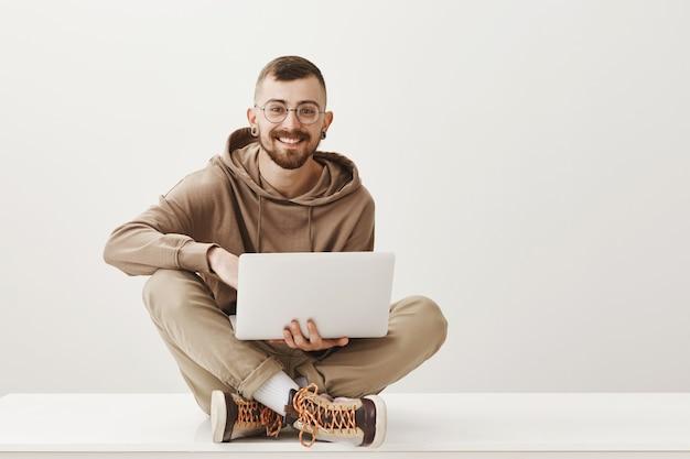 Homem bonito e sorridente sentado de pernas cruzadas e trabalhando no laptop