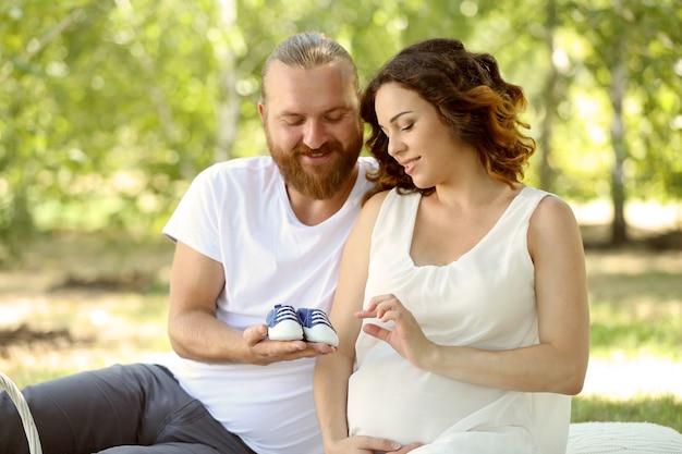 Homem bonito e sua adorável esposa grávida com botinhas de bebê azul no parque