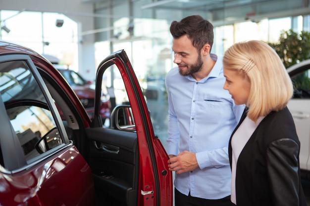Homem bonito e sua esposa olhando para dentro de um carro novo para venda na concessionária, copie o espaço