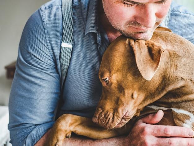 Homem bonito e um filhote de cachorro encantador. fechar-se