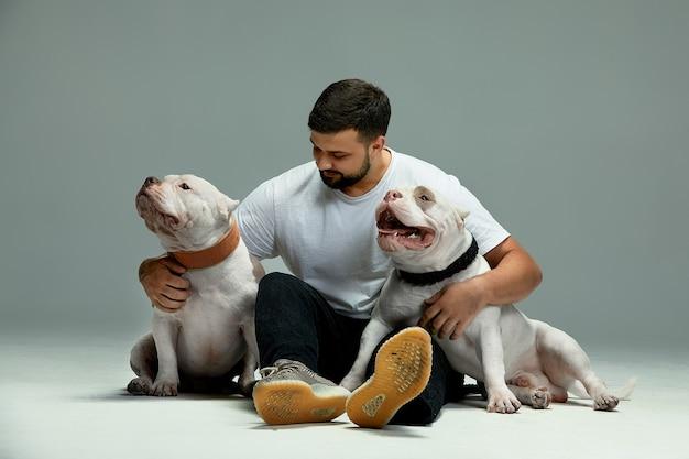 Homem bonito e um valentão encantador de cães. close-up, dentro de casa. foto de estúdio, cor branca. conceito de cuidado, educação, treinamento de obediência e criação de animais de estimação