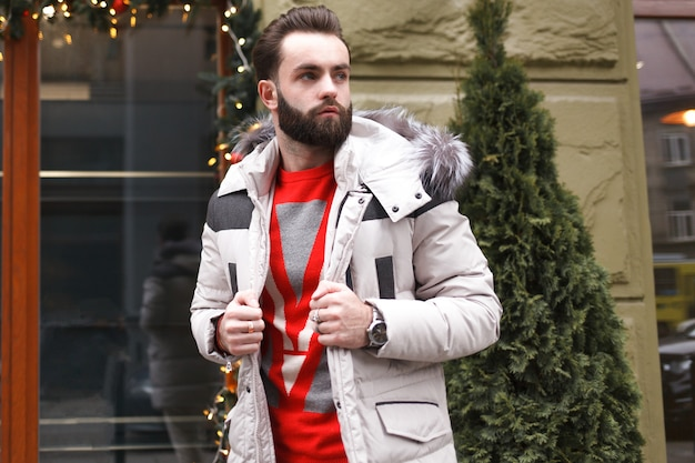 Homem bonito elegante com uma barba em uma jaqueta de inverno com peles posando ao ar livre.