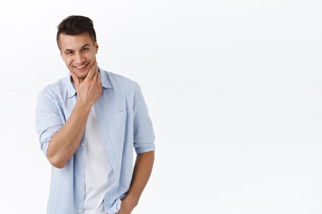 Homem bonito, elegante, confiante e inteligente em uma camisa branca, esfregando o queixo e olhando sob a testa com uma expressão atrevida de satisfação, verificando algo que ele gosta e aprova, tem uma ideia interessante