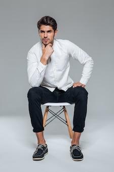 Homem bonito elegante e pensativo em uma camisa branca, sentado na cadeira sobre uma parede cinza