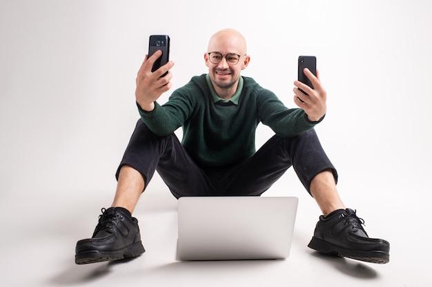 Homem bonito elegante homem com dois telefones nas mãos, sorrindo e olhando para eles no estúdio branco.