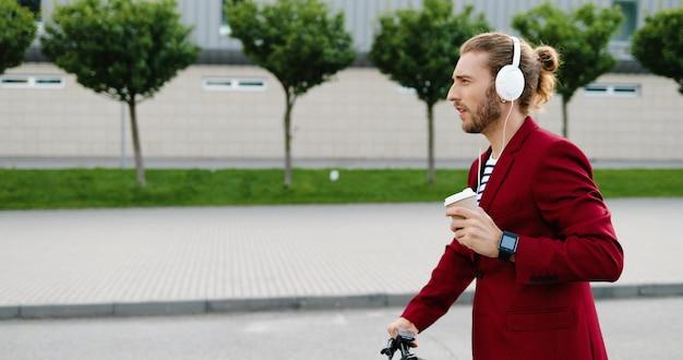 Homem bonito elegante jovem caucasiano em fones de ouvido, dirigindo a scooter elétrica na rua, ouvindo música e bebendo a bebida. veículo andando de cara e bebendo café ao ar livre. passeio pela cidade.