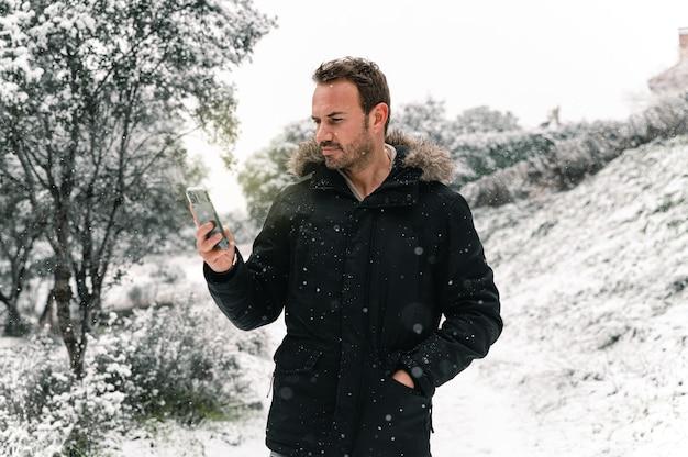 Homem bonito em agasalhos em pé na floresta de inverno com neve e mensagens no smartphone