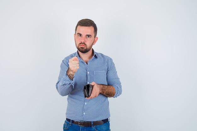 Homem bonito em camisa, jeans segurando a carteira, mostrando o gesto de figo e olhando sério, vista frontal.