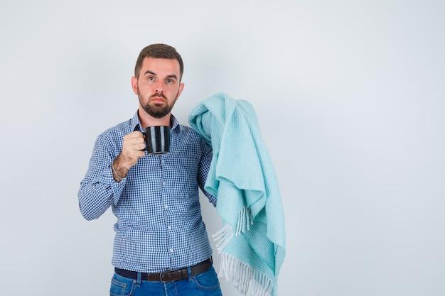 Homem bonito em camisa, jeans, segurando uma xícara de chá em uma mão, xale na outra mão e olhando sério, vista frontal.