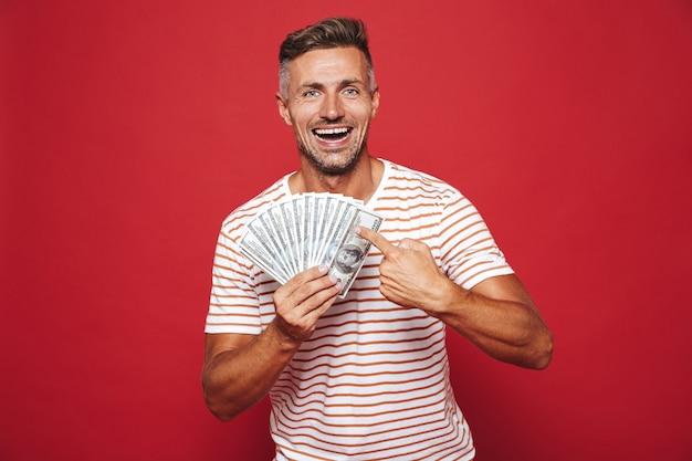Homem bonito em camiseta listrada sorrindo e segurando leque de notas de dinheiro isoladas no vermelho