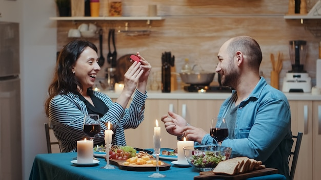 Homem bonito em casamento com a namorada durante o jantar festivo, na cozinha, sentado à mesa bebendo uma taça de vinho tinto. mulher feliz e surpresa sorrindo e abraçando-o.