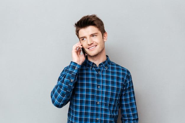 Homem bonito em cima de parede cinza e falando por telefone.