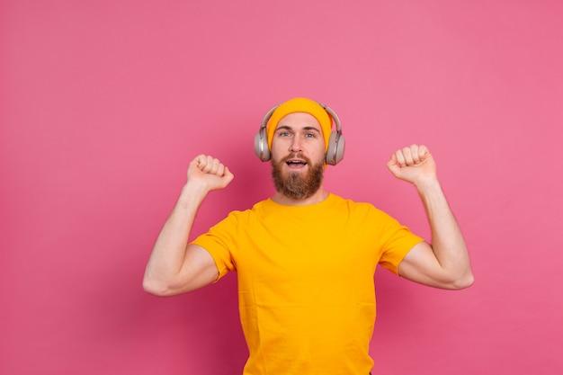 Homem bonito em dança casual com fones de ouvido isolados em fundo rosa