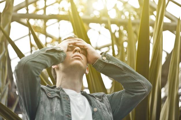 Homem bonito em depressão. hipster não barbeado em um jardim botânico, segurando sua cabeça. conceito: dor de cabeça e sofrimento.