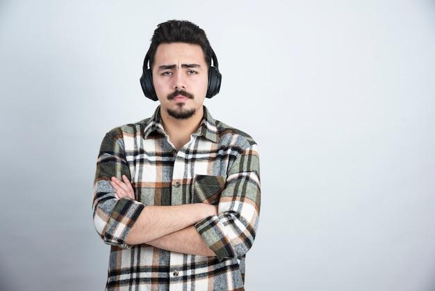 Homem bonito em fones de ouvido, ouvindo música, parede branca.