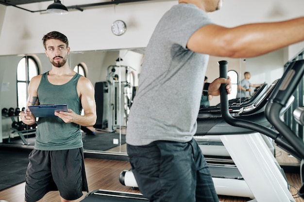 Homem bonito em forma controlando homem maduro e suado malhando em uma máquina elíptica na academia