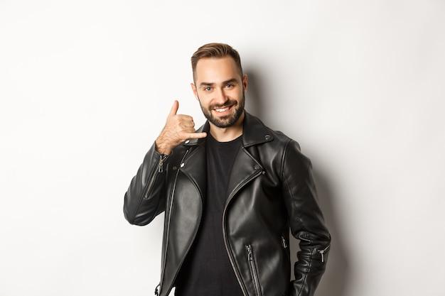 Homem bonito em jaqueta de couro flertando com você, mostrando o gesto de me ligar no celular, em pé
