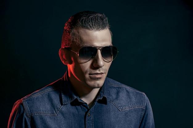 Homem bonito em óculos escuros e camisa jeans