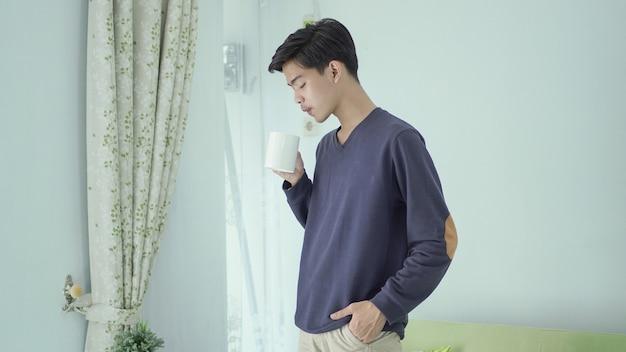 Homem bonito em pé bebendo um copo de bebida em casa