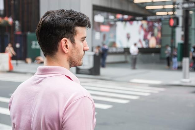 Homem bonito em pé perto da estrada