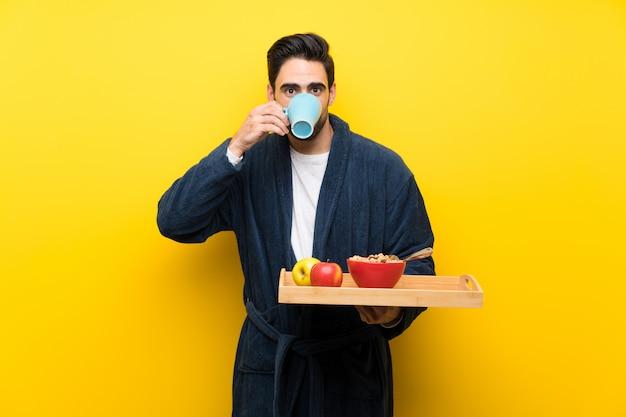 Homem bonito em pijama sobre parede amarela isolada