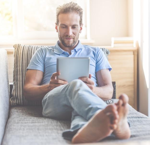 Homem bonito em roupas casuais está usando um tablet digital