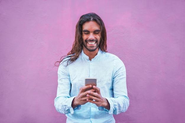 Homem bonito em roupas casuais, usando um aplicativo de smartphone com parede roxa no fundo - cara moderno se divertindo com as novas tendências da tecnologia - conceito de geração social e tecnológica - foco em seu rosto