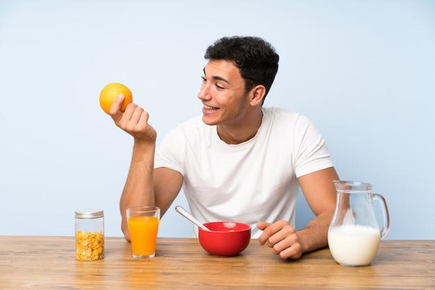 Homem bonito em tomar café da manhã e segurando uma laranja