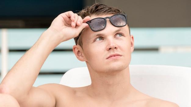 Homem bonito em topless com óculos de sol.
