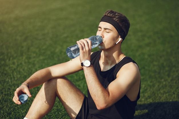 Homem bonito em um clother de esportes bebendo água em um parque