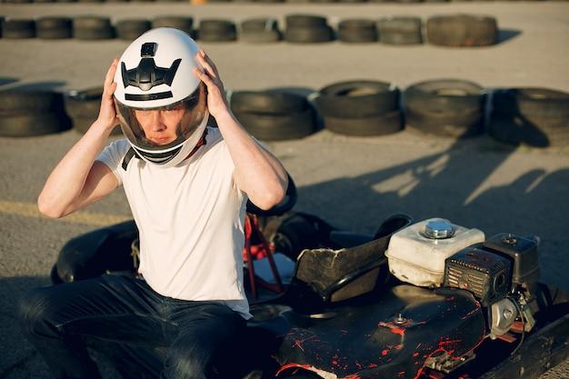 Homem bonito em um kart com um carro