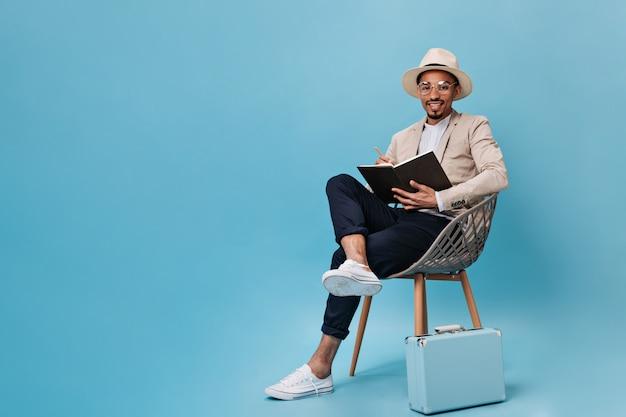 Homem bonito em um terno bege segurando um caderno e posando em uma cadeira na parede azul