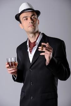 Homem bonito em um terno de negócio com uísque e charuto.
