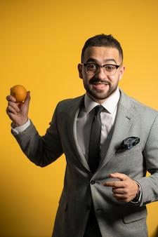 Homem bonito em um terno elegante, usando óculos com laranja em uma mão levantada em pé isolado no fundo amarelo.