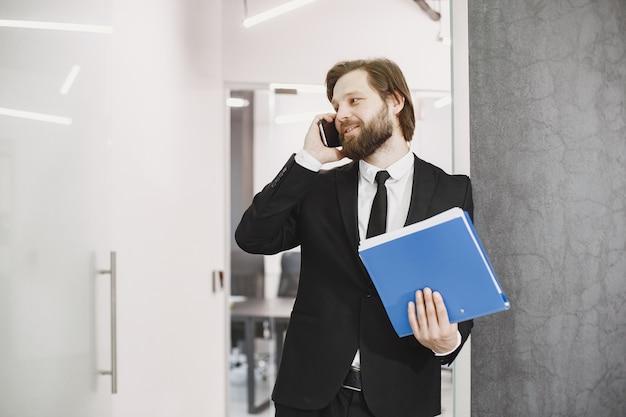 Homem bonito em um terno preto. empresário com telefone celular.