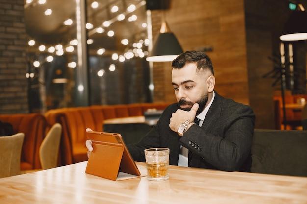 Homem bonito em um terno preto, trabalhando em um café