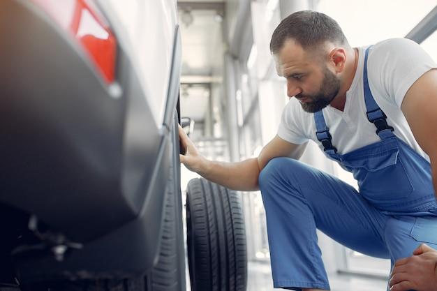 Homem bonito em um uniforme azul verifica o carro