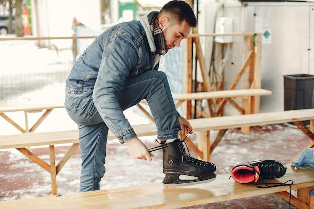 Homem bonito em uma arena de gelo com skate