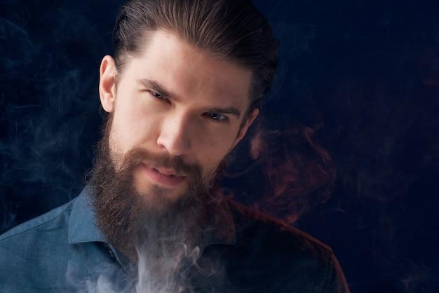 Homem bonito em uma camisa preta com nuvens de fumaça isoladas no fundo.